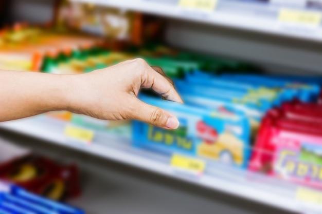 Mano de mujer elegir o tomar productos dulces, aperitivos en los estantes en la tienda de conveniencia