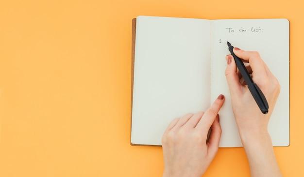 La mano de la mujer escribe una lista de tareas con un bolígrafo en un bloc de notas en blanco