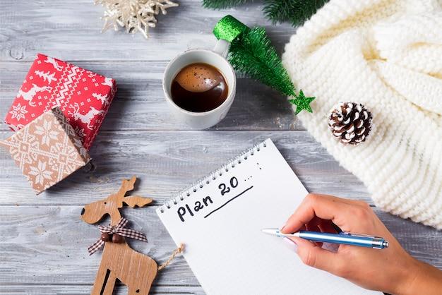 Mano de mujer escribiendo en el bloc de notas saludos de navidad con taza de té, decoración en madera