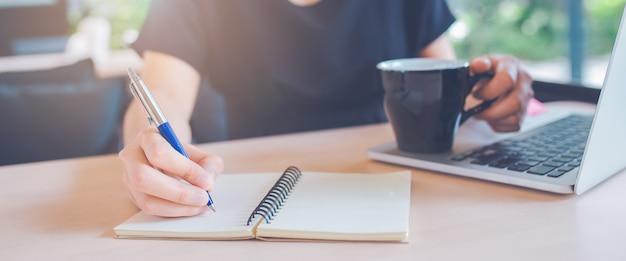 La mano de la mujer está escribiendo en un cuaderno con una pluma en oficina. bandera de la tela.