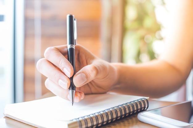 La mano de la mujer está escribiendo en una libreta en blanco con una pluma en un escritorio de madera