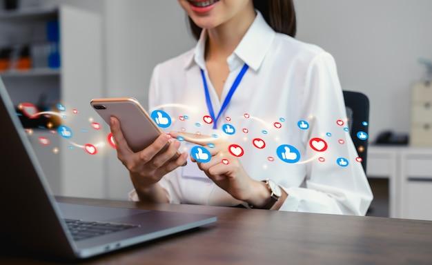 Mano de mujer escribiendo mensajes de texto en línea social y mostrando el icono en la pantalla.