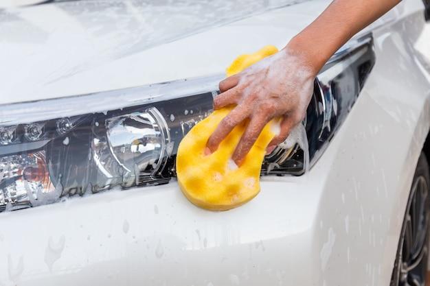 Mano de mujer con esponja amarilla lavado faro coche moderno o automóvil de limpieza.