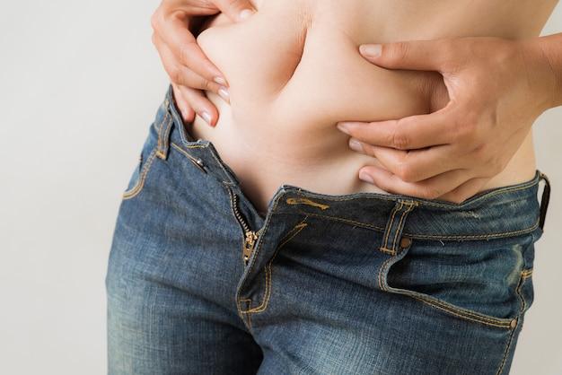 Mano de mujer gorda sosteniendo su propia grasa del vientre.