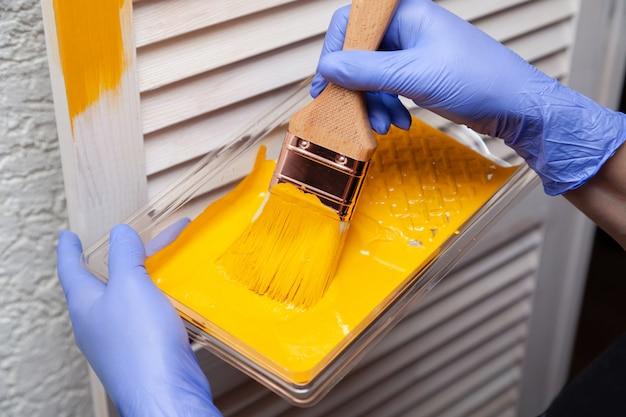 Mano de mujer en guante de goma con pincel pintando puerta de madera con pintura amarilla