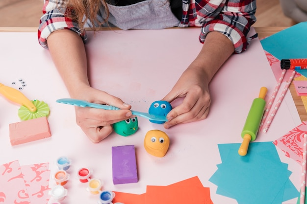 Mano de mujer haciendo caras creativas de dibujos animados usando arcilla colorida