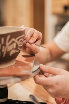Mano de mujer haciendo diseño en tazón pintado.