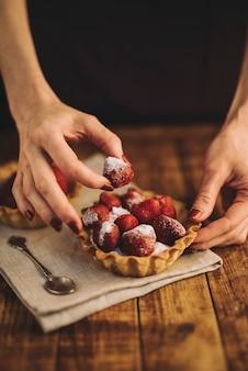 Mano de mujer haciendo tarta de fresas en mesa de madera