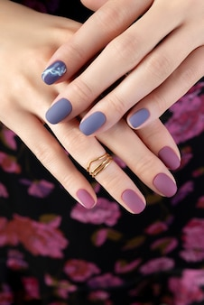 Mano de mujer hermosa con manicura mate púrpura sobre tela.