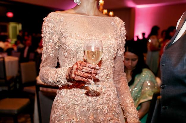 La mano de la mujer india pintada con mehndi sostiene una copa de vino