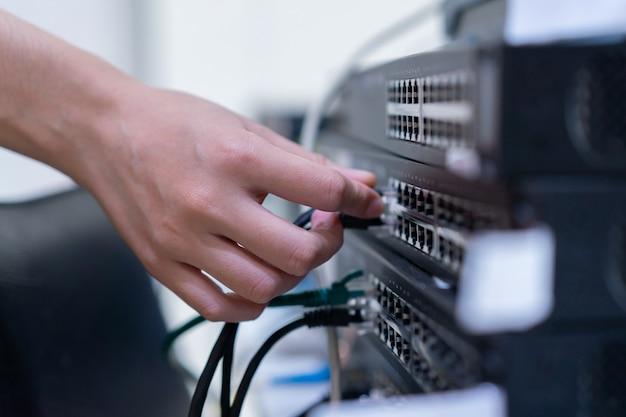 Mano de mujer de ingeniería que intenta conectar lan para cambiar la capa 2 para compartir archivos y redes