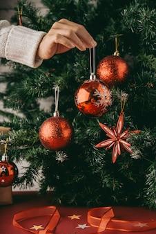 Mano de mujer irreconocible con adorno delante del árbol de navidad