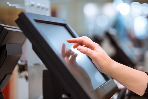 Mano de mujer joven haciendo pago de proceso en una caja registradora con pantalla táctil, concepto de finanzas