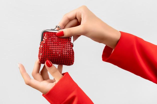La mano de la mujer joven hermosa con manicura roja sostiene la billetera en gris