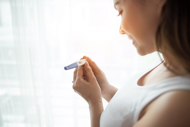 Mano de mujer joven con prueba de embarazo