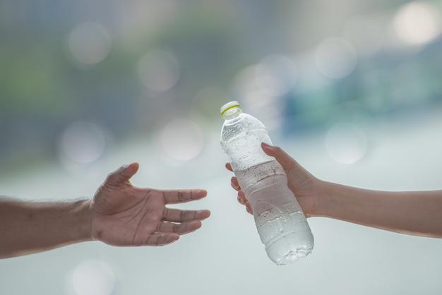 Mano de la mujer joven que da o que sirve una botella de agua potable fría fresca a un hombre después del ejercicio de la aptitud.