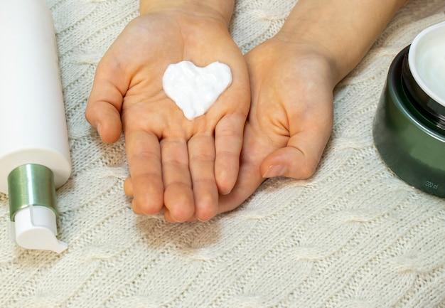 La mano de una mujer joven saca una crema facial del frasco. cuidado de la piel, hidratación y nutrición.