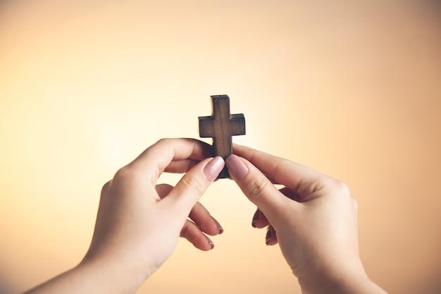 Mano de mujer joven, tenencia, cruz de madera