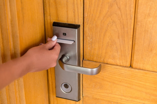 Mano de mujer con keycard en la cerradura electrónica.