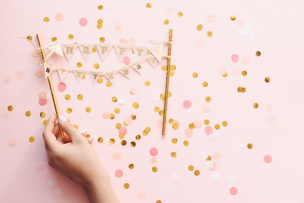 La mano de la mujer con la manicura en colores pastel sostiene una pequeña pancarta feliz cumpleaños. saludos de feliz cumpleaños sobre fondo rosa con confeti