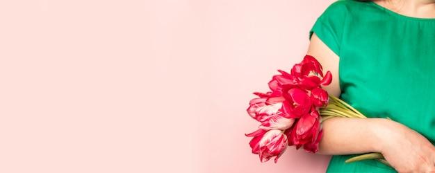 La mano de la mujer con la manicura que sostiene tulipanes florece en fondo rosado.