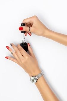 Mano de mujer con manicura roja sosteniendo una botella de esmalte de uñas