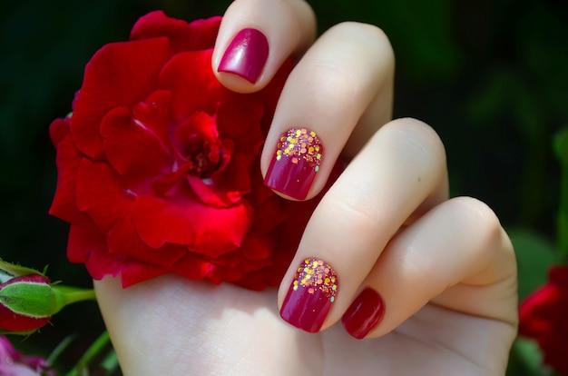 Mano de mujer con manicura rosa brillo