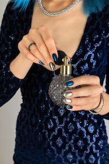 Mano de mujer con manicura sosteniendo una botella de fondo de perfume. diseño de uñas plateadas de noche oscura de fiesta.