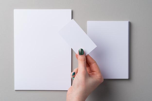 Mano de mujer con manicura con tarjeta blanca encima de la mesa
