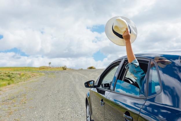 Mano de mujer manteniendo el sombrero en la ventana de la máquina