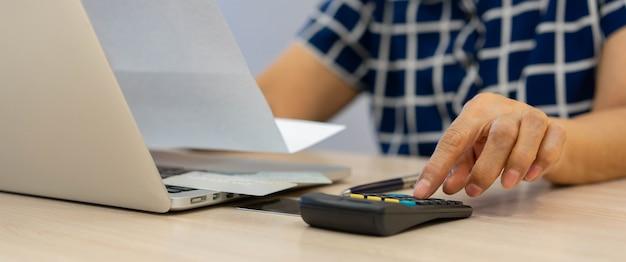 Mano de mujer mayor usando la calculadora para calcular para planificar el gasto de dinero sobre el estilo de vida de las pensiones