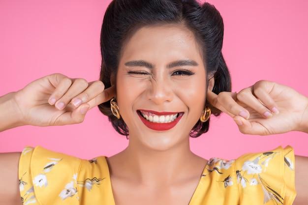 La mano de la mujer de la moda cubre sus oídos