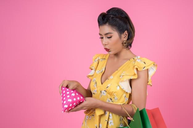 Mano de la mujer de la moda de los jóvenes que sostiene la cartera y los panieres