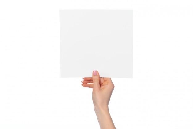 Mano de mujer mostrando banner de papel blanco aislado en blanco