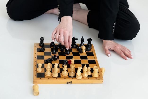 La mano de la mujer mueve la pieza de ajedrez en el tablero de ajedrez de madera antiguo