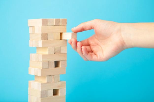 La mano de la mujer de negocios escoge y pone el bloque de la última pieza del rompecabezas de madera. bloque de madera sobre fondo azul.