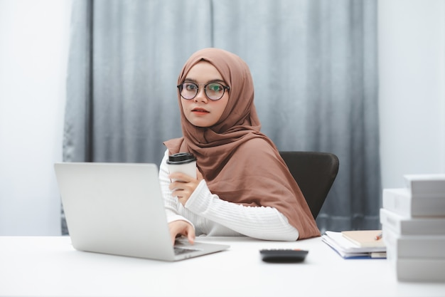Mano de mujer de negocios musulmana atractiva sosteniendo una taza de café mientras trabaja en la oficina en casa.