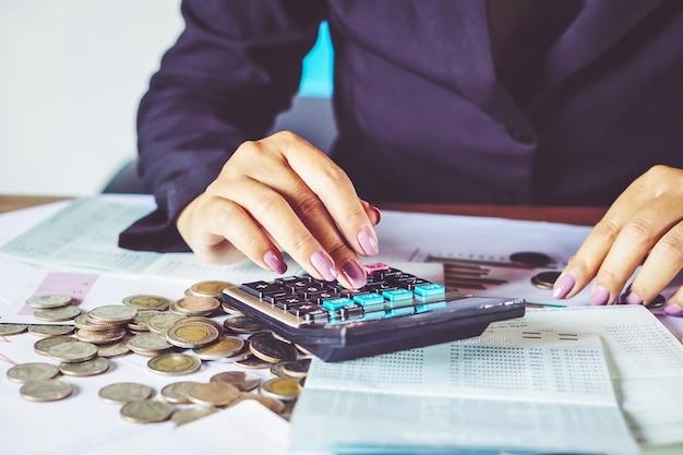 Mano de la mujer de negocios que calcula el dinero del ahorro