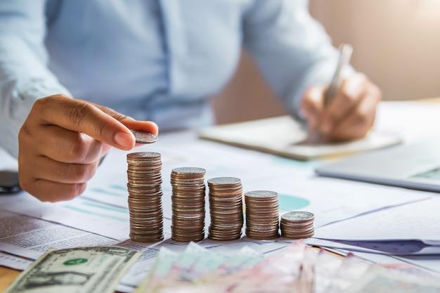 Mano de la mujer de negocios que sostiene monedas para apilar en finanzas del dinero del ahorro del concepto del escritorio