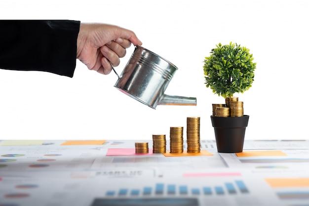 Mano de mujer de negocios regando monedas y dinero creciendo