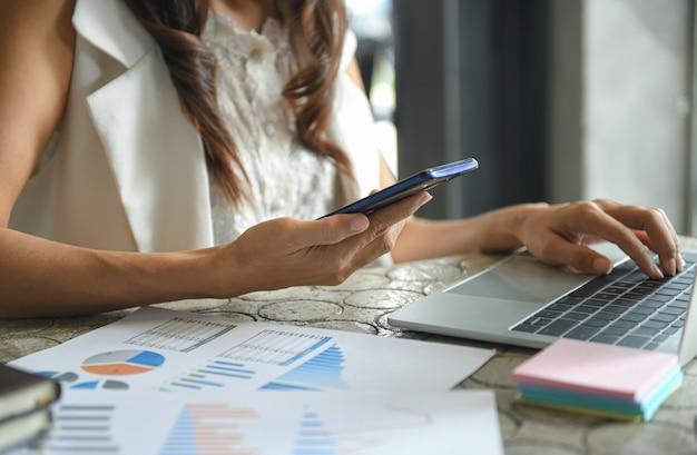 La mano de una mujer de negocios está utilizando un teléfono móvil para encontrar información.