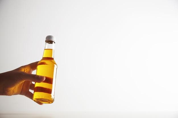 Mano de mujer ofrece botella transparente de cristal con refresco en el interior