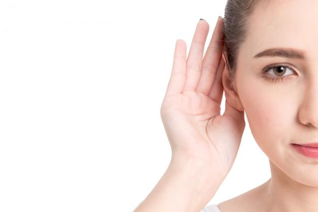 Mano de la mujer en el oído que escucha para el sonido reservado aislado en el fondo blanco