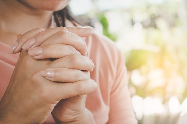 Mano de mujer orando pacíficamente al aire libre en la mañana