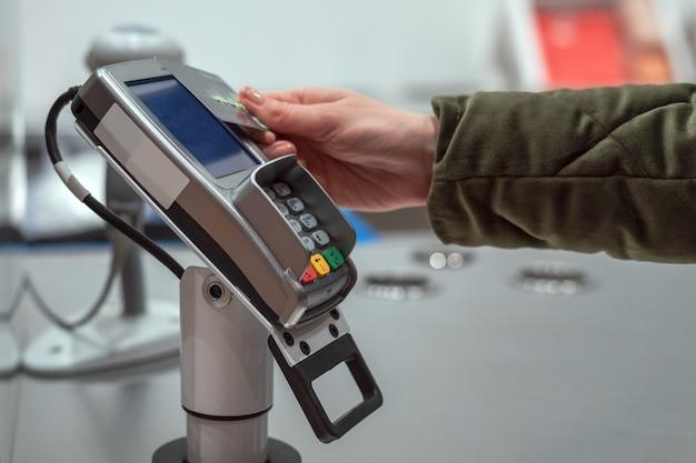 La mano de la mujer paga las compras en la tarjeta de la tienda sin contacto, tecnología inalámbrica, pago
