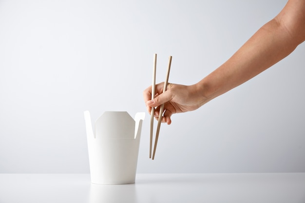 Mano de mujer con palillos cerca de la caja de comida para llevar en blanco con fideos sabrosos aislados en blanco presentación del conjunto por menor