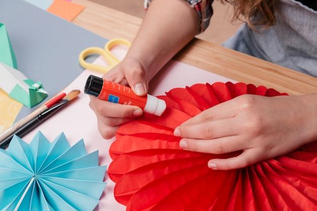 Mano de mujer pegando papel de origami mientras hace flor de origami