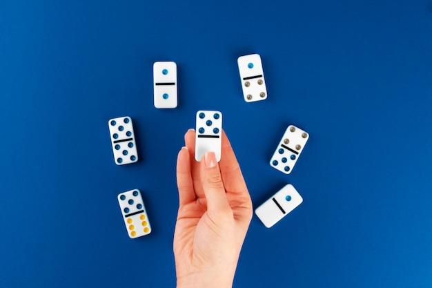 Mano de mujer con pieza de dominó sobre fondo azul, vista superior