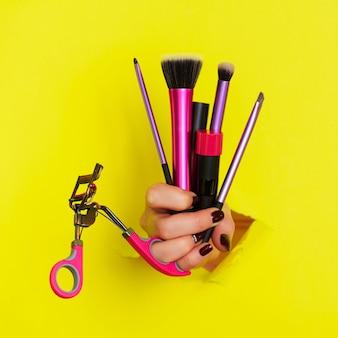 Mano de mujer con pinceles, rímel, lápiz labial, rizador de pestañas para maquillaje