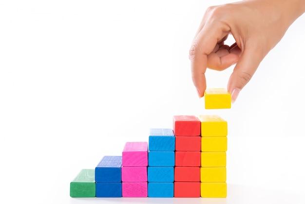 Mano de mujer pone bloques de madera en forma de escalera, concepto de negocio